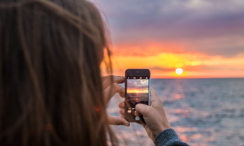 Woman taking photo of sunset with phone
